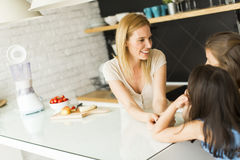 Woman and two girls in the kitchen Stock Photos