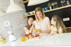 Woman and two girls in the kitchen Stock Photography