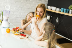 Woman and two girls in the kitchen Royalty Free Stock Photo