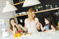 Woman and two girls in the kitchen Stock Image