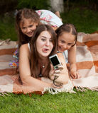 Woman and two girls making faces and doing photos at park Stock Photo