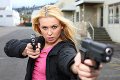 Woman with two guns stock images