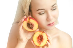 Woman with two halves of peach and a towel on her head. Woman with two halves of a peach and a towel on his head. Her eyes closed. Beauty. Horizontal photo royalty free stock photos
