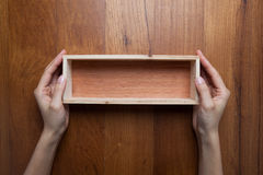 A woman two hands hold a empty opened wooden box Royalty Free Stock Image