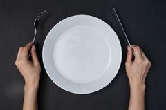 Woman two hands hold a knife and fork and white dish on black ba stock image