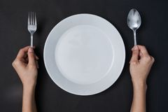 Woman two hands hold a spoon and fork and white dish on black ba stock photos