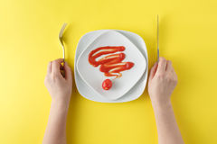 Woman two hands hold a spoon and fork and white dish on yellow b royalty free stock photos