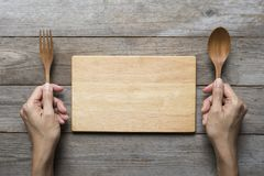 Woman two hands hold a spoon and fork and wood dish on table bac Stock Photos