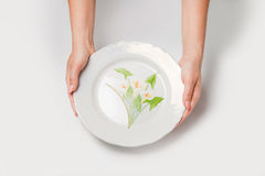 Woman two hands hold a white dish (plate) isolated white and top Royalty Free Stock Photography