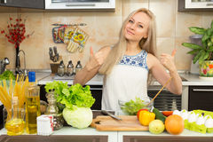Woman with two hands thumbs up at the kitchen table Stock Photos
