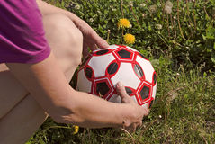 Woman with two hands wipes the soccer ball on the grass Royalty Free Stock Photos