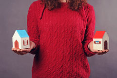 Woman and two houses in hands Royalty Free Stock Photography