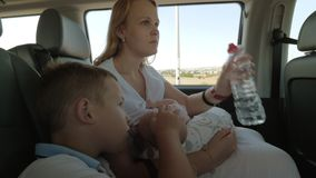 Woman with two kids traveling by car. Family of three traveling by car. Woman breastfeeding baby and drinking water while her elder son stroking head of his stock video