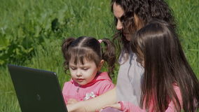Woman with two little girls with a laptop in the park. Happy family in nature on a sunny day. Mom with daughters on green grass wi stock video