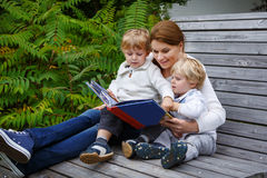 Woman and two little siblings sitting on bench in park and readi Royalty Free Stock Images