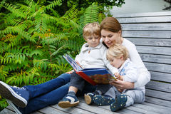 Woman and two little siblings sitting on bench in park and readi Stock Image