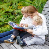 Woman and two little siblings sitting on bench in park and readi Royalty Free Stock Photography