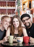 Woman with two male friends in a coffee house Stock Images