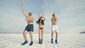 A woman and two men dance with arms up on the snow while wearing just swimwear. 4K. A woman and two men dance with arms up on the snow while wearing just stock footage