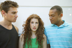 Woman between two men. Woman flirting with two men Stock Photos