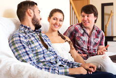 A woman and two men smiling. Polyandry: a beautiful women and two men smiling indoors Stock Photos