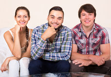 A woman and two men smiling. Polyandry: a happy women and two men smiling indoors Royalty Free Stock Photos