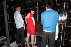 Woman and two men standing at mens urinal Stock Photography
