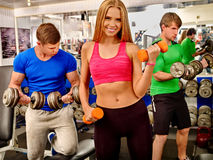 Woman and two men working with dumbbells. Happy blonde women and two men concentrated work with dumbbells in the gym Stock Photo