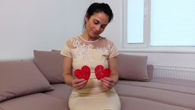 Woman with two paper heart. In room stock video