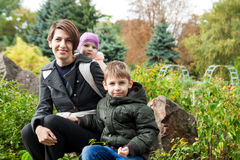 Woman with two siblings in park Stock Photo