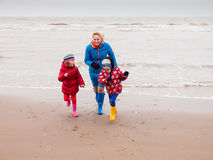 Woman and two small children playing on winter beach Royalty Free Stock Photos
