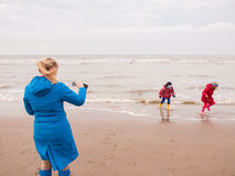 Woman and two small children playing on winter beach Stock Photography