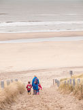 Woman and two small children walking down to the beach Royalty Free Stock Photo