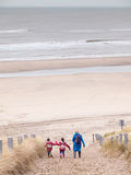 Woman and two small children walking down to the beach Stock Image