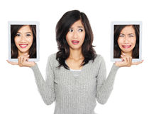 Woman with two tablet computer screen. one with smiling face and Stock Photography