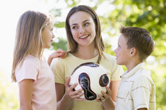 Woman and two young children holding volleyball Stock Photo