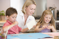 Woman and two young children in kitchen with art p royalty free stock images