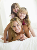 Woman and two young girls in bed playing Stock Images
