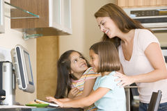 Woman and two young girls in kitchen with computer Royalty Free Stock Images