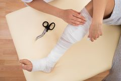 Woman tying bandage on patient's leg Royalty Free Stock Photo
