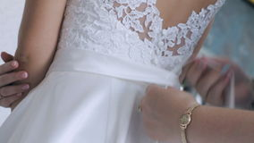 Woman tying bow on the bride`s dress close-up. Woman tying bow on the bride`s dress back close-up stock footage