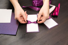 Woman tying a bow on a handmade card Stock Photography