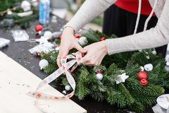Woman tying a bow ribbon, decorated a Christmas wreath. Attaches toys and decor with glue gun. Hands close-up. Master. Manufacturer of Christmas wreath from royalty free stock photo