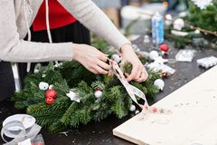 Woman tying a bow ribbon, decorated a Christmas wreath. Attaches toys and decor with glue gun. Hands close-up. Master. Manufacturer of Christmas wreath from stock photos