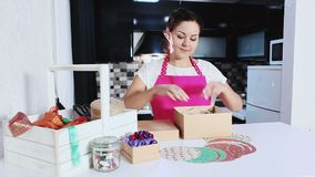 Woman tying gift box with decorating ribbon. Preparing for celebrating Christmas holidays at home. Young housewife in apron making Christmas gift stock video footage