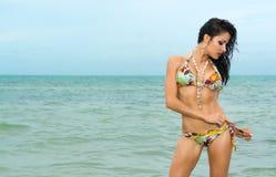Woman tying her bikini at the seaside Royalty Free Stock Photos