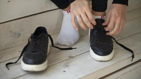 Woman is tying her shoes indoor. Sportswoman is tying her laces on sneakers sitting on the steps. She is getting ready for a run stock video footage