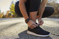 Woman tying her sports shoe in street, low section close up Royalty Free Stock Photos