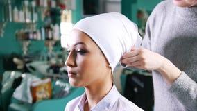 Woman tying islamic wedding turban for beautiful model. Close up stock video