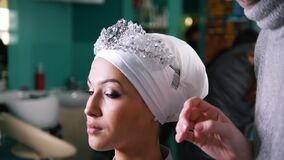 Woman tying islamic wedding turban for beautiful model. Woman tying islamic wedding turban with diadem for beautiful model, close up stock footage